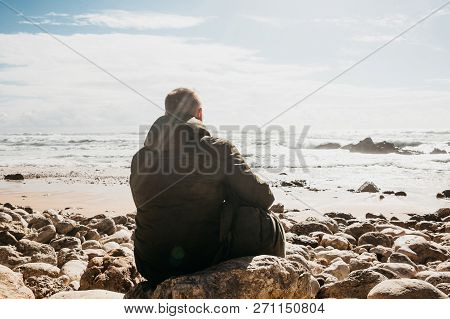 A Man With A Backpack Or A Tourist Or A Traveler In Solitude Admires A Beautiful View Of The Atlanti