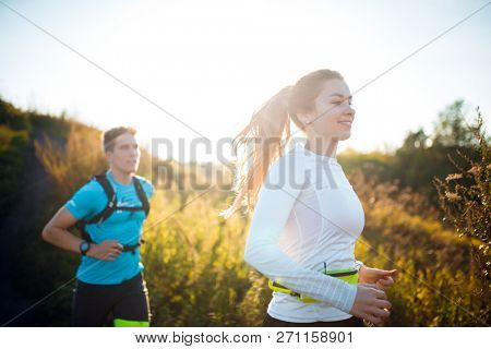 Image of young sports women and men running along footpath