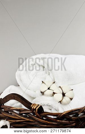Laundry Basket Filled White Fluffy Towels, Cotton Flowers And A Bottle Of Liquid Soap Against A Grey