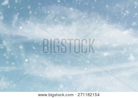 Snowy Wintry Sky. Blurred Background Of Snow Falling Against Cool Blue Cloudy Sky During A Winter St