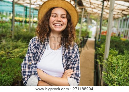 Portrait of young florist woman 20s posing and working in greenhouse over plants