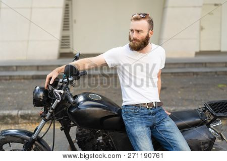 Dull Biker Upset About Breakdown And Waiting Roadside Assistance. Bearded Young Man Sitting On Motor