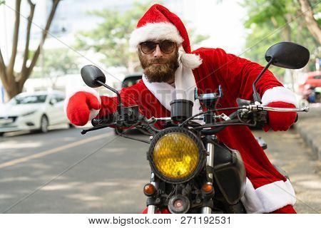 Serious Handsome Christmas Biker Posing On Motorbike. Bearded Young Man In Santa Costume Starting Mo