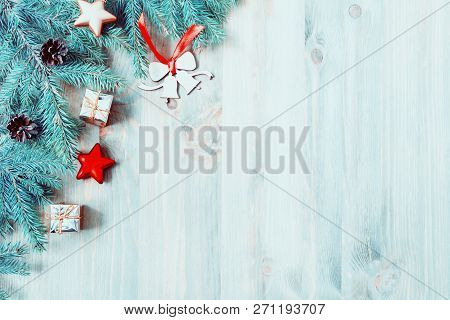 New Year and Christmas background. Christmas toys, blue fir tree branches on the wooden background. New Year and Christmas composition, space for text