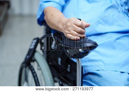 Asian Senior Or Elderly Old Lady Woman Patient On Electric Wheelchair With Remote Control At Nursing