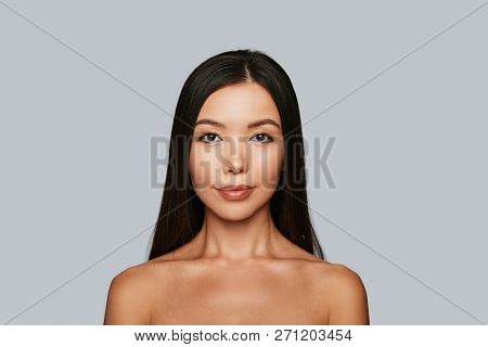 Glowing With Natural Beauty. Beautiful Young Asian Woman Looking At Camera And Smiling While Standin