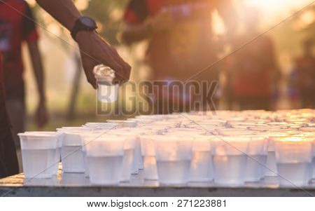 Marathon Runner Take A Water At A Service Point In A Marathon Race With Sunrise, Selective Focus, Sh