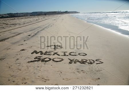 Words in sand. Mexico 500 yards with Arrow pointing towards Mexico written in the sand at the border between Mexico and the United States of America. Directional Signage.