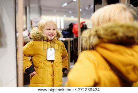 Cute Little Boy Trying New Coat During Shopping. Fashion Warm Clothes For Fall Or Winter. Kid/child