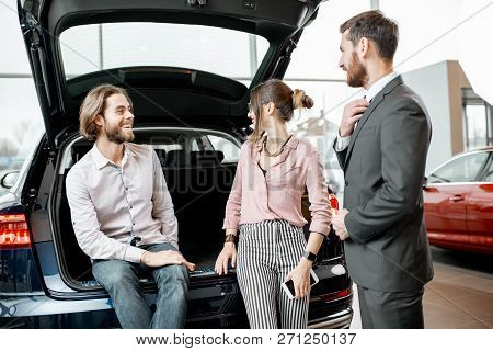 Young Couple Sitting In The Trunk Of A New Car Listening To The Salesman At The Showroom