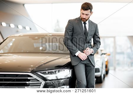Portrait Of An Elegant Businessman Standing Near The Luxury Car In The Showroom