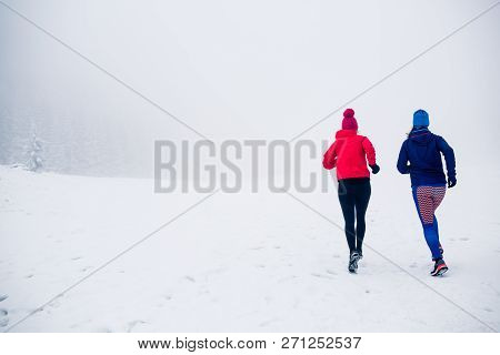 Girls Running Together On Snow In Winter Mountains. Sport, Fitness Inspiration And Motivation. Two W