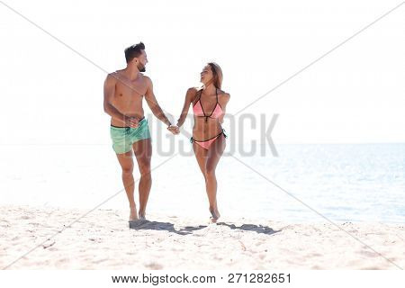 Playful couple holding hands and running on beach.