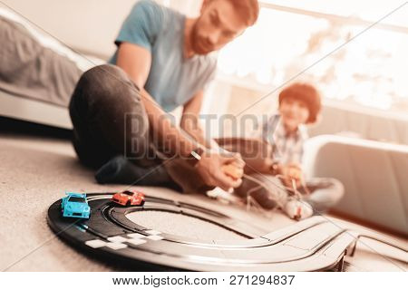 Bearded Father And Son Playing With Toy Race Road. Man Sitting On Floor. White Carpet In Room. Toy C