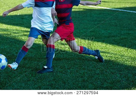Football Teams - Boys In Red, Blue, White Sportswear Play Soccer On The Green Field. Boys Dribbling.