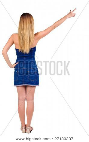 back of view beautiful young  woman in jeans dress pointing at wall. rear view. Isolated over white .