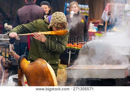 Hecha, Ukraine - Jan 27, 2018: Pork Butchers Competition. Boiling Cauldron On Fire. Pork Shoulder On