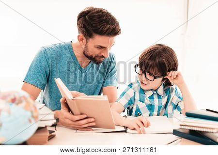 Little Boy In Glasses Doing Homework With Father. Education At Home. White Table In Room. Sitting Bo