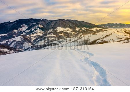Winding Foot Path Through Snowy Slope In Mountains. Gorgeous Winter Landscape At Sunrise With Cloudy