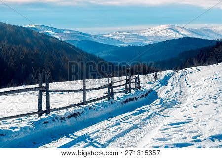 Country Road In To The Winter Mountains. Wooden Fence Along The Road. Composite Image