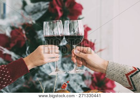Cropped View Of The Hands Of A Woman And A Man Toasting With Wine Glasses On Christmas Time With A F