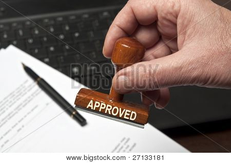 Approved stamp in male hand