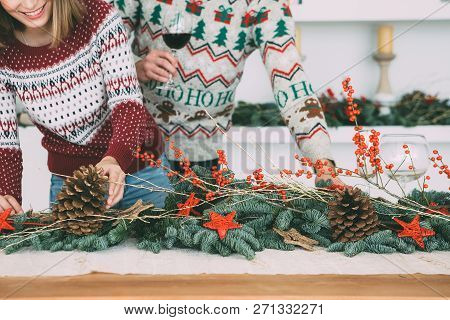 Cropped View Of A Young Woman Is Decorating A Table With Christmas Ornaments With A Young Man With A