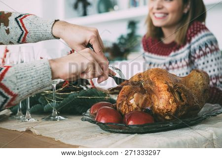 Cropped View Of The Hands Of A Man Carving A Roasted Turkey On A Christmas Table Decorated With Orna