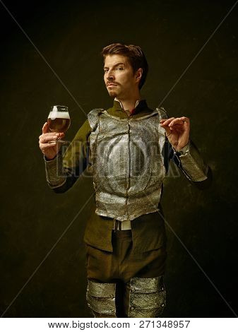 Medieval Knight With Beer On Dark Studio Background. Portrait In Low Key Of Brutal Man In Tradishion