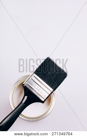Brush With Black Handle On Open Can Of White Paint On Grey Background. Renovation Concept. Top View.