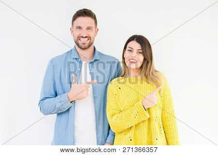 Young beautiful couple togheter over isolated background cheerful with a smile of face pointing with hand and finger up to the side with happy and natural expression on face