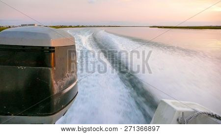 Wake And Waves And Close Up Of An Outboard Engine In Coastal Waters At Sunset With Marsh Grass In Th