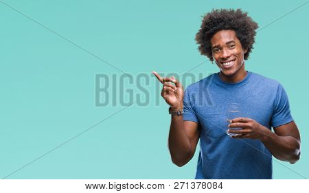 Afro american man drinking glass of water over isolated background very happy pointing with hand and finger to the side