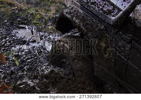 poster of Fragment of car stuck in dirt, close up. Wheel in deep puddle of mud overcomes obstacles. Offroad tire covered with mud on nature background. Reduced gear concept.