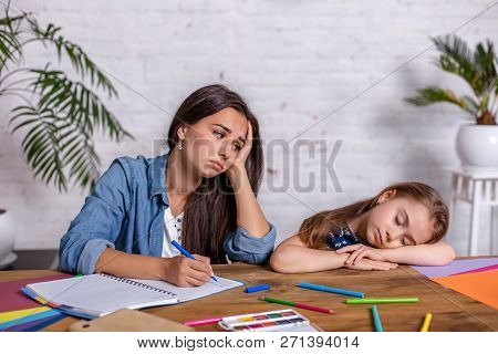 Mother Becoming Frustrated With Daughter Whilst Doing Homework Sitting At The Table At Home In Learn