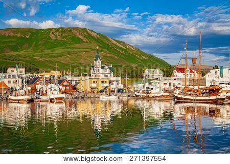 Scenic View Of The Historic Town Of Husavik In Beautiful Golden Evening Light At Sunset With Blue Sk