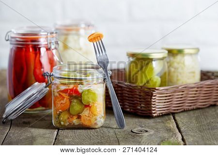 Autumn seasonal pickled vegetables in glass jars, on rustic wooden background.