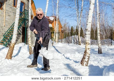 Senior Man Throwing Snow With Shovel From Private House Yard In Winter On Bright Sunny Day. Elderly