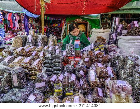 Vendor Sitting At Local Market