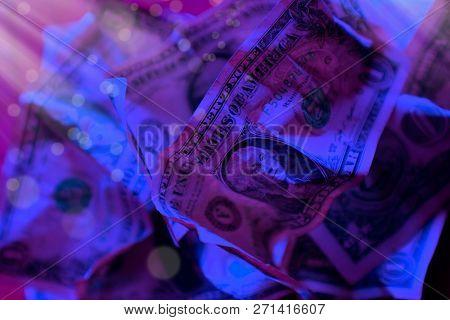 close up wrinkled American one dollar bills under colorful lights