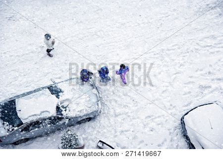 Elevated view of children play in snow covered parking lot