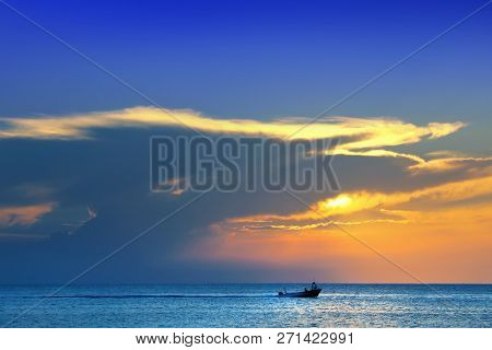Colorful seascape image with shiny sea and speedboat over cloudy sky and sun during sunset in Cozumel, Mexico