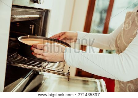 Woman Puts The Homemade Cake In The Oven