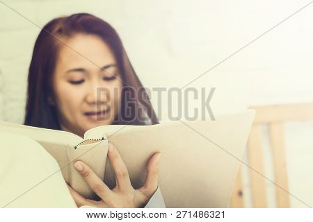 Women Read Book To Learning On Bed In Bed Room In The Morning.color Tone