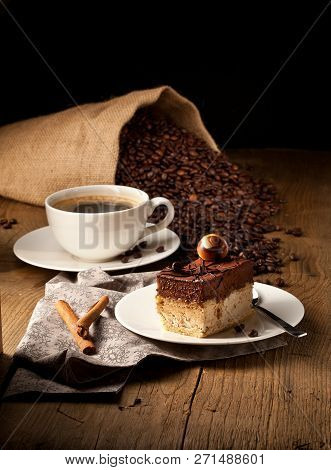 Chocolate Cake On Wooden Table With A Coffee Cup.
