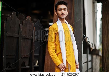 Indian Stylish Man In Yellow Traditional Clothes With White Scarf Posed Outdoor.