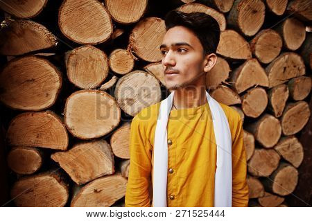 Indian Stylish Man In Yeallow Traditional Clothes With White Scarf Posed Outdoor Against Wooden Stum