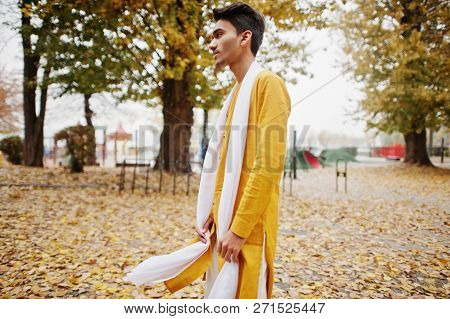 Indian Stylish Man In Yeallow Traditional Clothes With White Scarf Posed Outdoor Against Autumn Mood