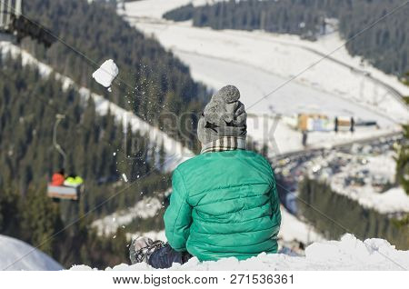 Boy Sits On Snowy Slope Of A Hill And Throws Snowball Against The Background Of Cable Car, Coniferou