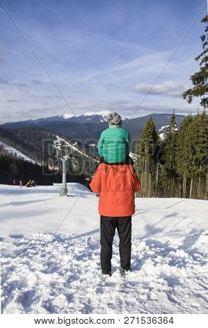 Father With Son On Shoulders Stands Against The Backdrop Of Mountains, Cable Lift And Coniferous For